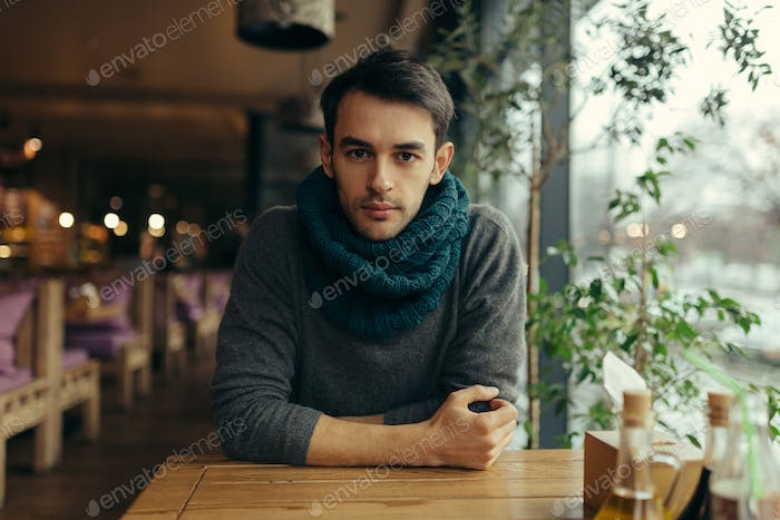 Image of handsome young man in restaurant
