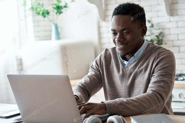 Smiling african american man using laptop computer working from home office.