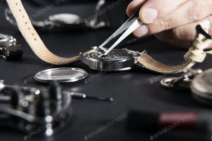 Detail der Arbeit eines Uhrmachers, der eine Batterie ersetzt