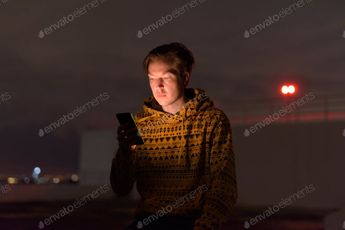 Young handsome man using phone at rooftop of the building during stormy weather at night