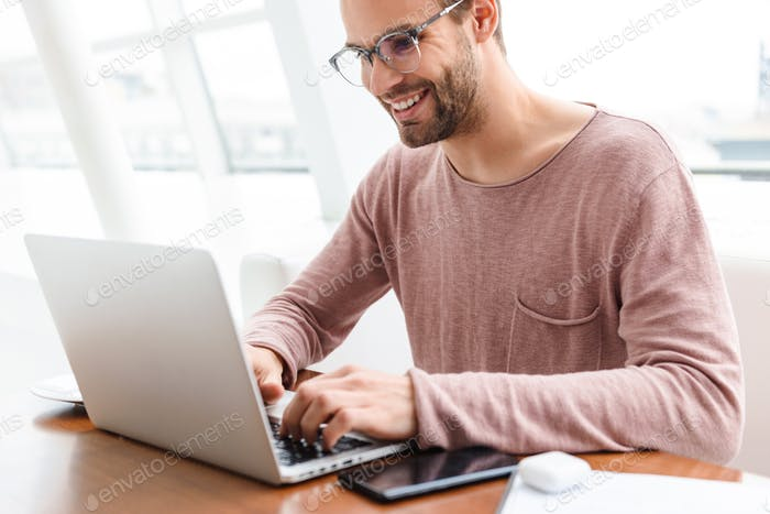 Image of young bearded man wearing eyeglasses working on laptop in cafe