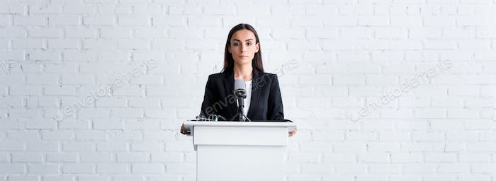 attractive, confident lecturer holding on podium tribune in conference hall