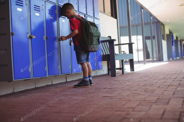 Full length of boy leaning on lockers in corridor