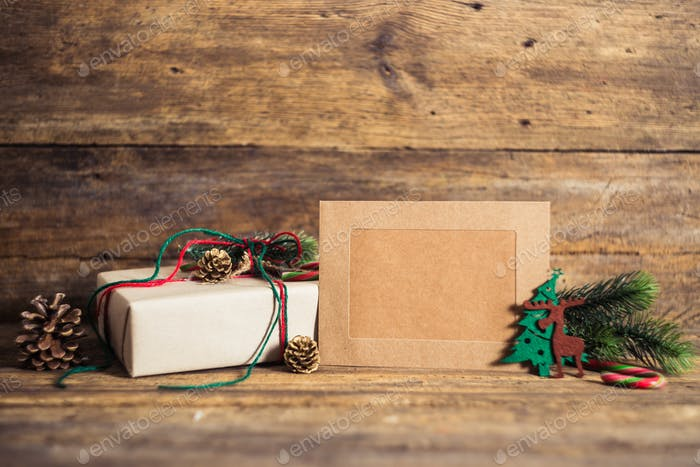 Christmas gift box with cards  on a wooden background with candy