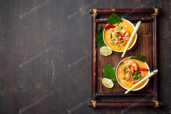 Shrimps Tom Yam Kung in white bowls on autentic thai tray top view