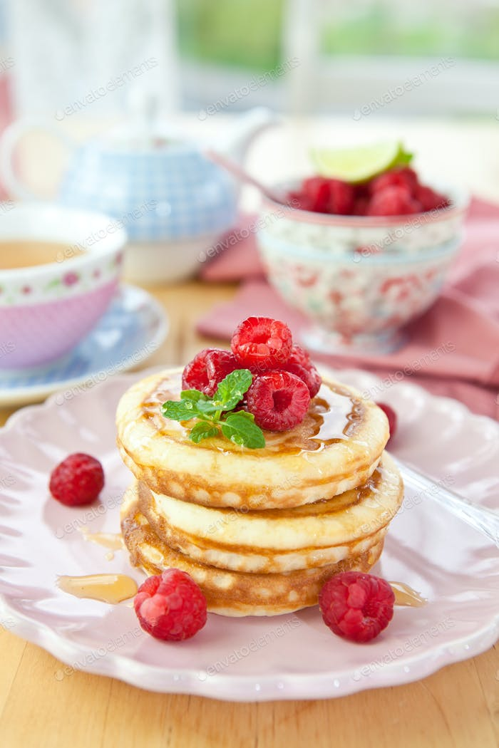 A stake of pancakes with fresh raspberries