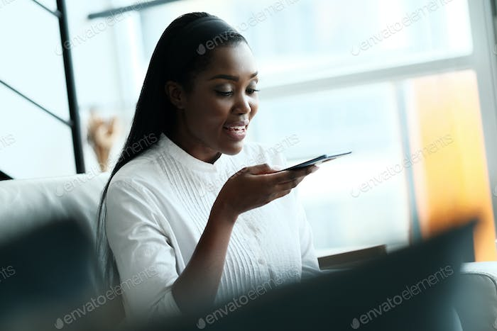 Black Woman Using Mobile Phone For Voice Mail