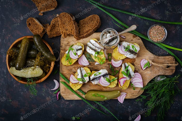 Appetizer of herring anchovy and baked potato. Flat lay. Top view