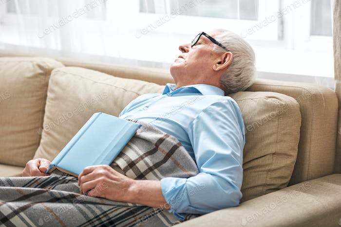 Tired senior man covered with plaid napping on couch with open book