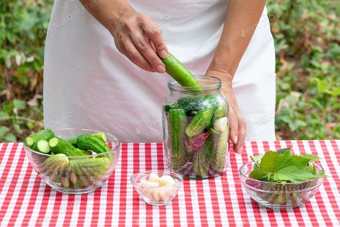 Female cook puts fresh cucumber in a glass jar for preservation