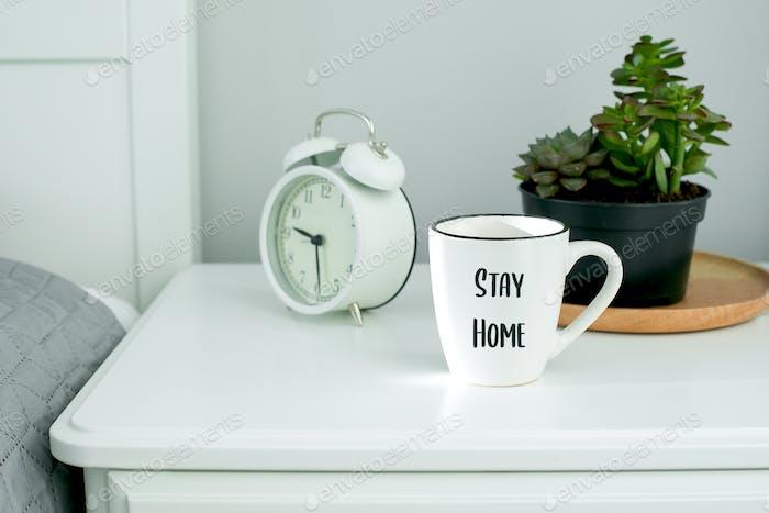 Morgen zu Hause Routine. Weiße Tasse mit Kaffee, Wecker und saftiger Topfpflanze