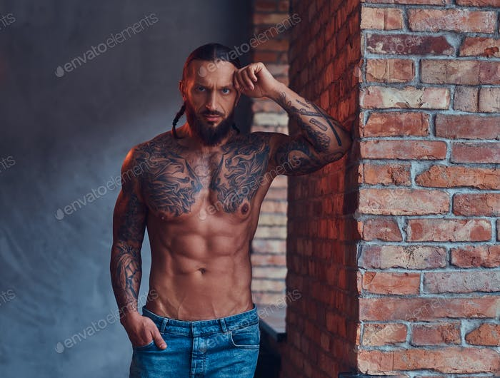 Handsome tattooed man with a stylish haircut and beard standing against a brick wall