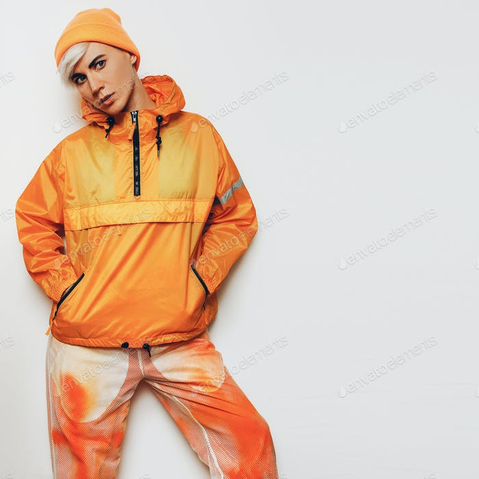Trendy Urban Outfit Tomboy girl in a bright orange sports clothi