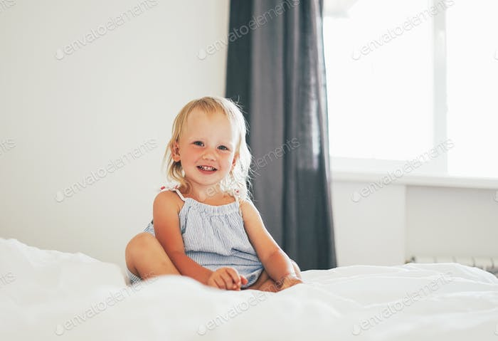 Cute blonde baby girl on bed in bright interior