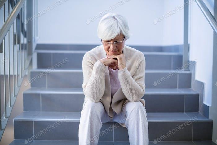 Upset senior woman sitting on stairs