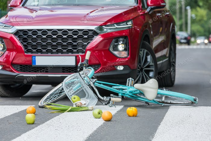 Groceries and a blue bike lies on the street next to the red car that caused the accident