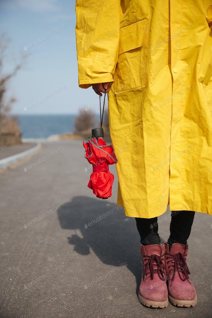 Schuss von Regenschirm und Frau Beine