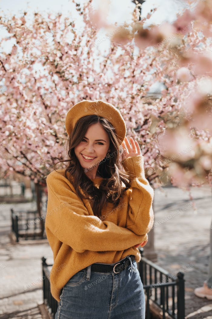 Positive lady in hat and sweater laughs against background of sakura. Optimistic woman in orange be