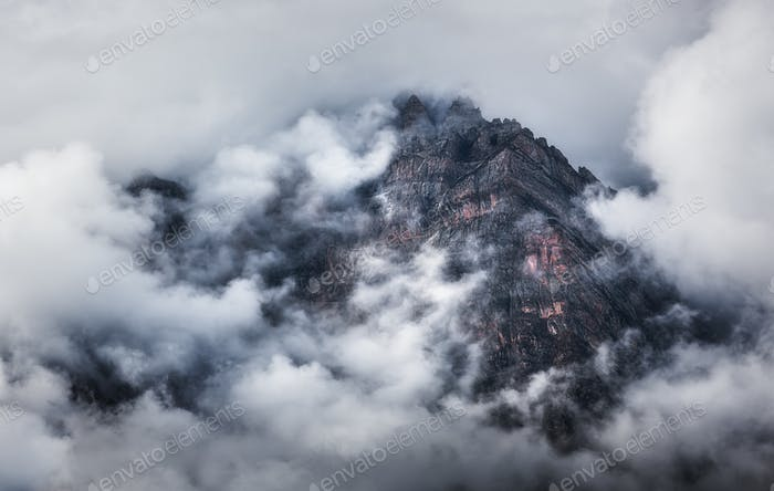 Majestical scene with mountains in clouds in overcast evening