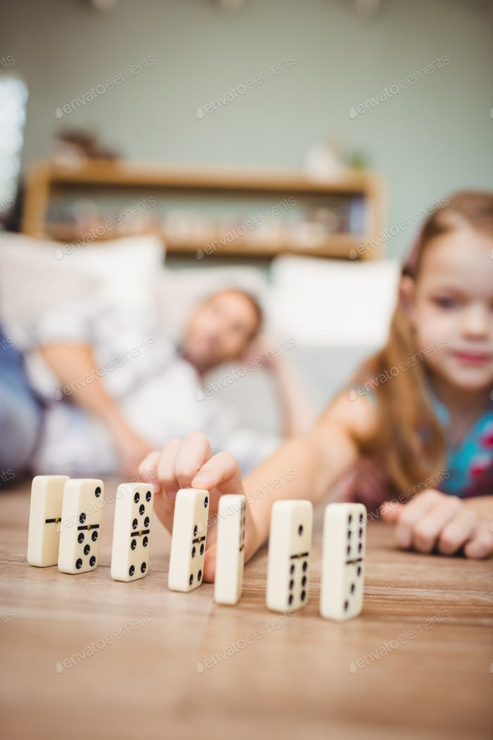 Close-up of girl arranging domino on hardwood floor at home