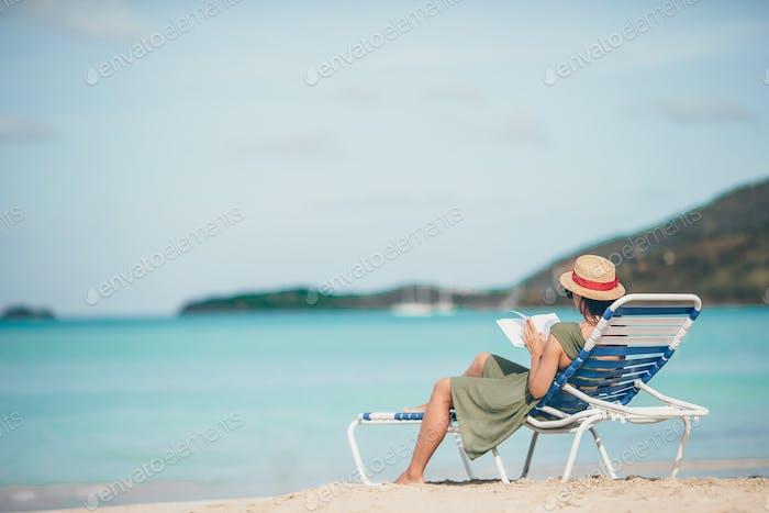 Junge Frau Lesen Buch auf Chaise-Lounge am Strand