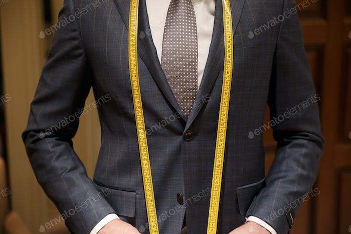 Обрезанное изображение человека с измерительной лентой на шее