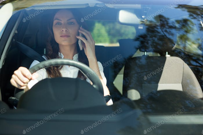 Woman talking on mobile phone while driving a car
