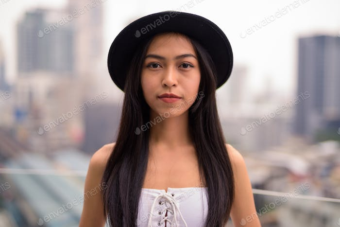 Young beautiful Asian tourist woman against view of the city