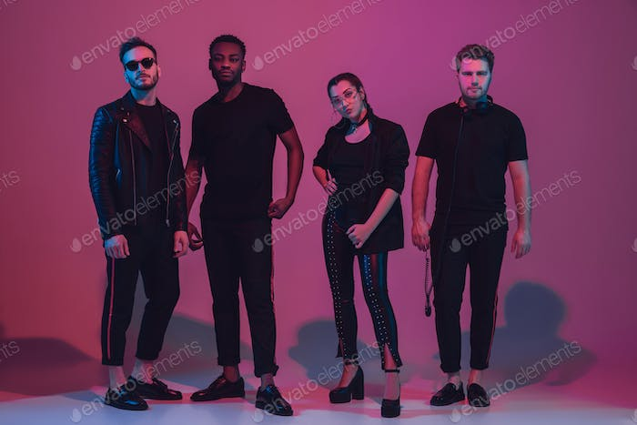 Group of young multiethnic musicians created band, dancing in neon light on pink background