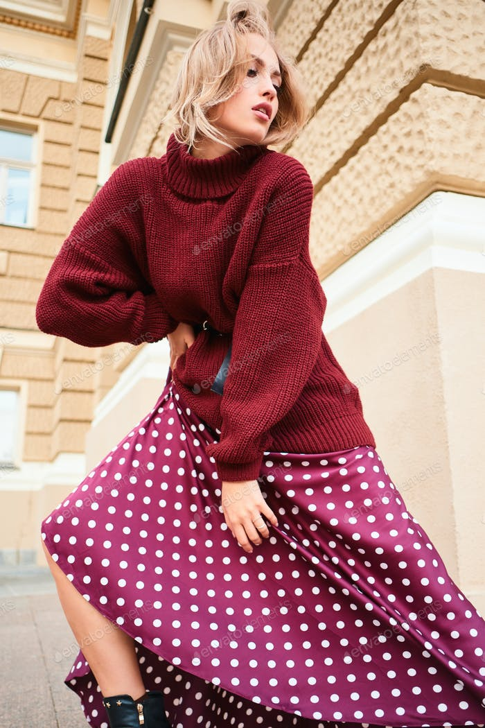 Conceptual shot of stylish blond girl in knitted sweater dreamily posing on street