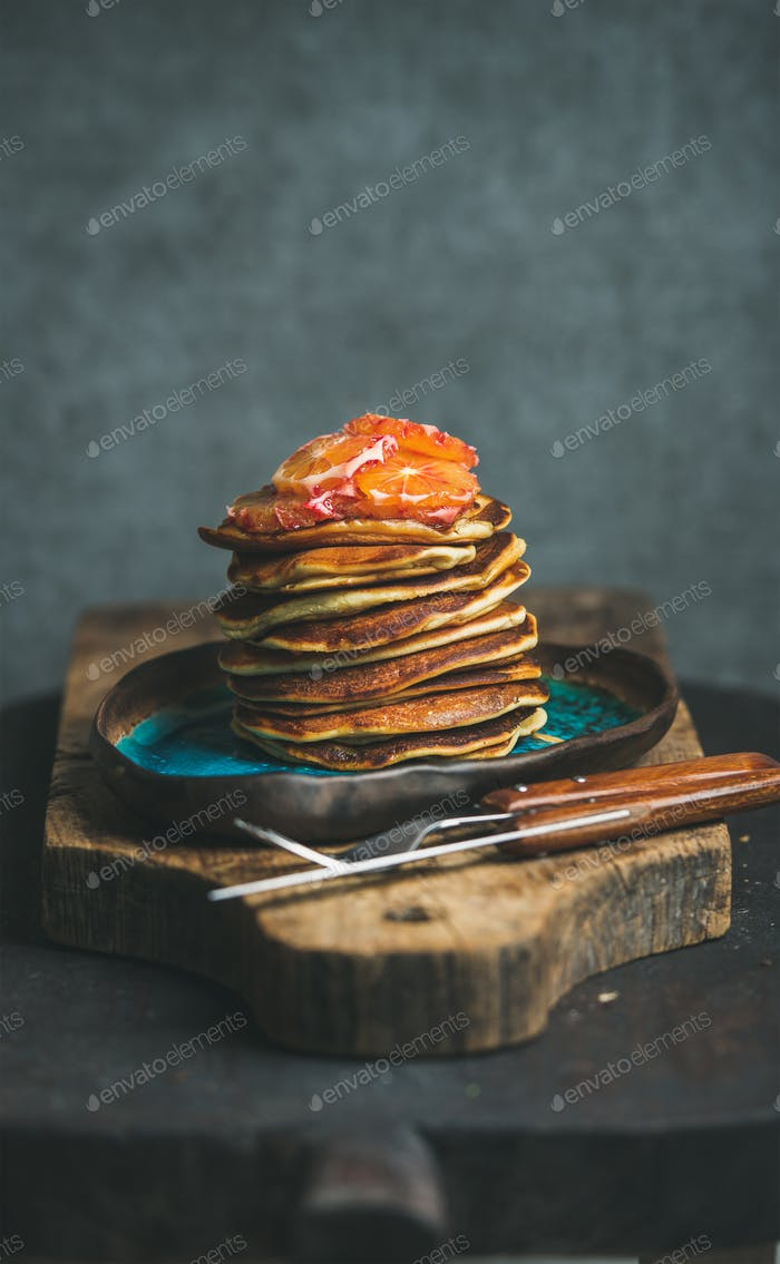 Pancakes with honey and bloody orange slices, copy space