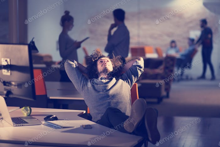 businessman sitting with legs on desk at office