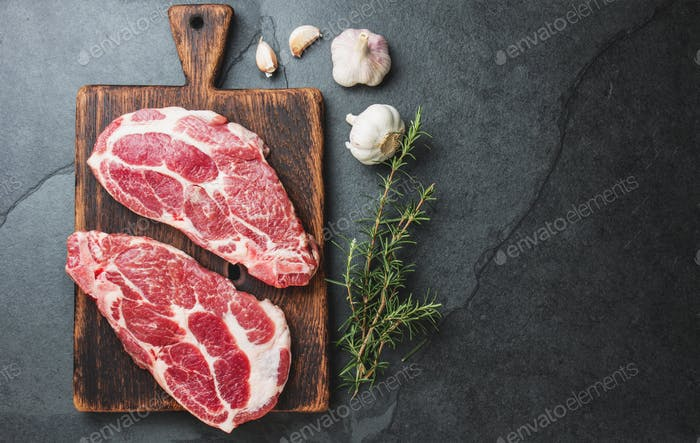 Raw pork steaks with seasoning on wooden board. Gray slate background.