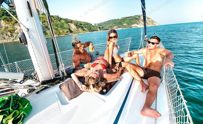 Junge reiche Freunde chillen auf Segelboot auf Seereise