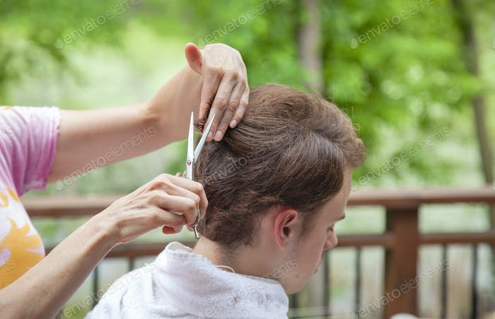 A teen boy gets a haircut from his mother outdoors during the pandemic