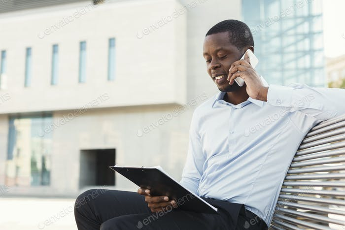 African-american businessman working with papers outdoors