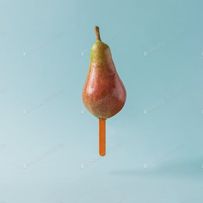 Pear with ice cream stick on pastel blue background. Food creative concept.