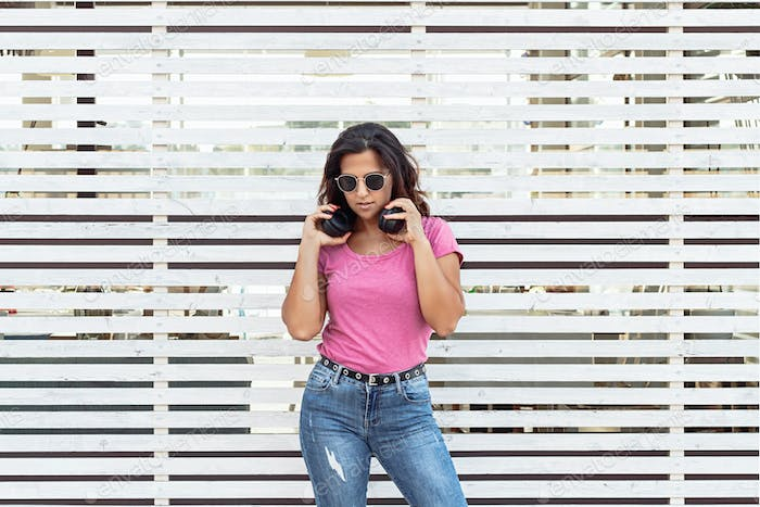 Place it - Young women with headphones and sunglasses stays near a geometric wall