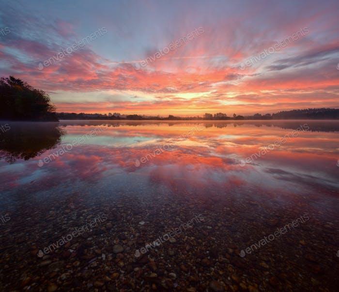Goldene Wolken beim Sonnenaufgang spiegelt sich in den ruhigen Gewässern eines l