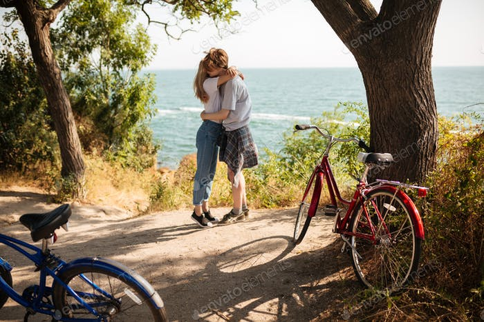 Beautiful couple embracing one another while standing in park with amazing sea view on background