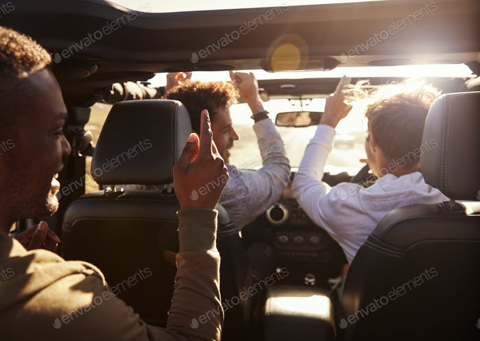 Three young adult men having fun driving an open top car