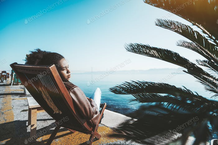 A girl on a deck chair, quayside