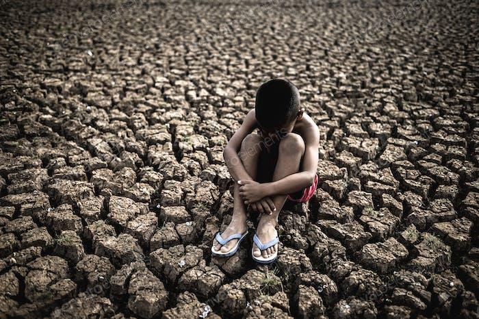 Men sitting hugging their knees, bent, bent on the dry soil,global warming