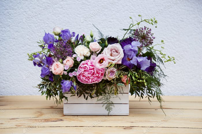 Beautiful tender bouquet of peonies in wooden box on rustic table
