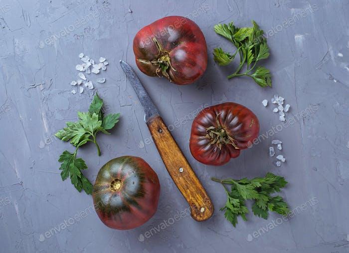 Tomaten, Salz, Petersilie und Messer auf grauem Betonuntergrund