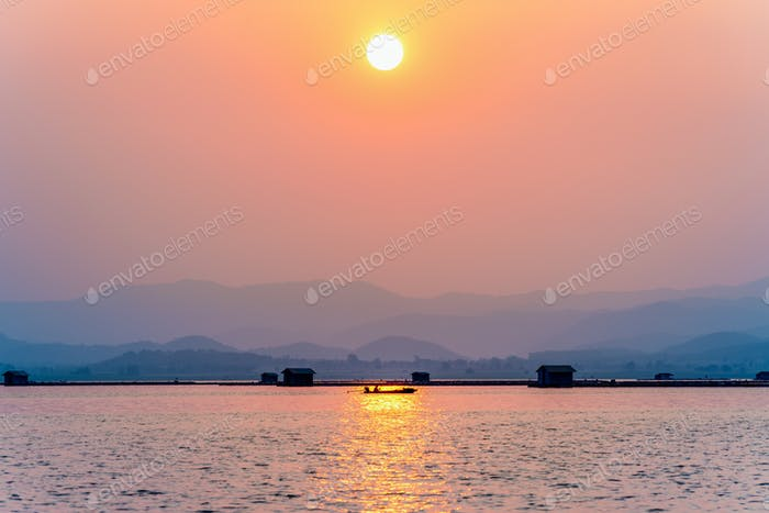 Fisherman driving a boat to home at sunset