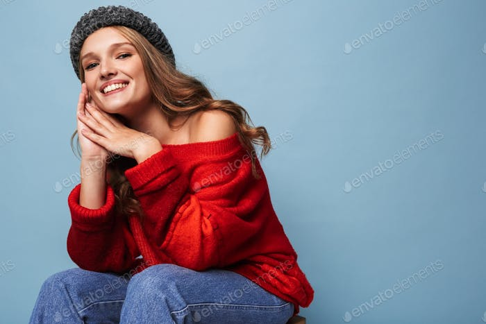 Beautiful smiling girl with wavy hair in hat and red sweater joyfully looking in camera