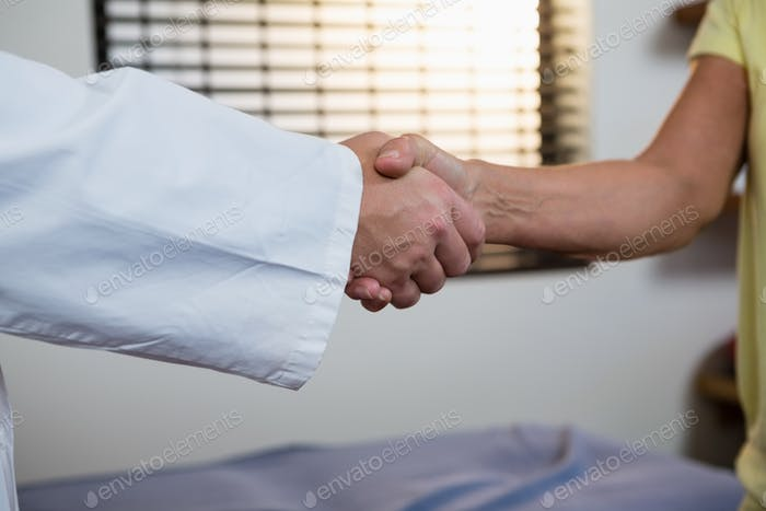 Physiotherapist shaking hand with patient
