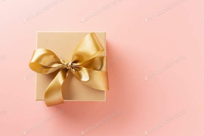 Geschenkbox mit goldenem Band auf rosa Hintergrund