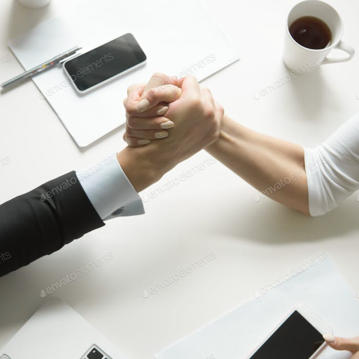 Businessman and businesswoman competing in arm wrestling